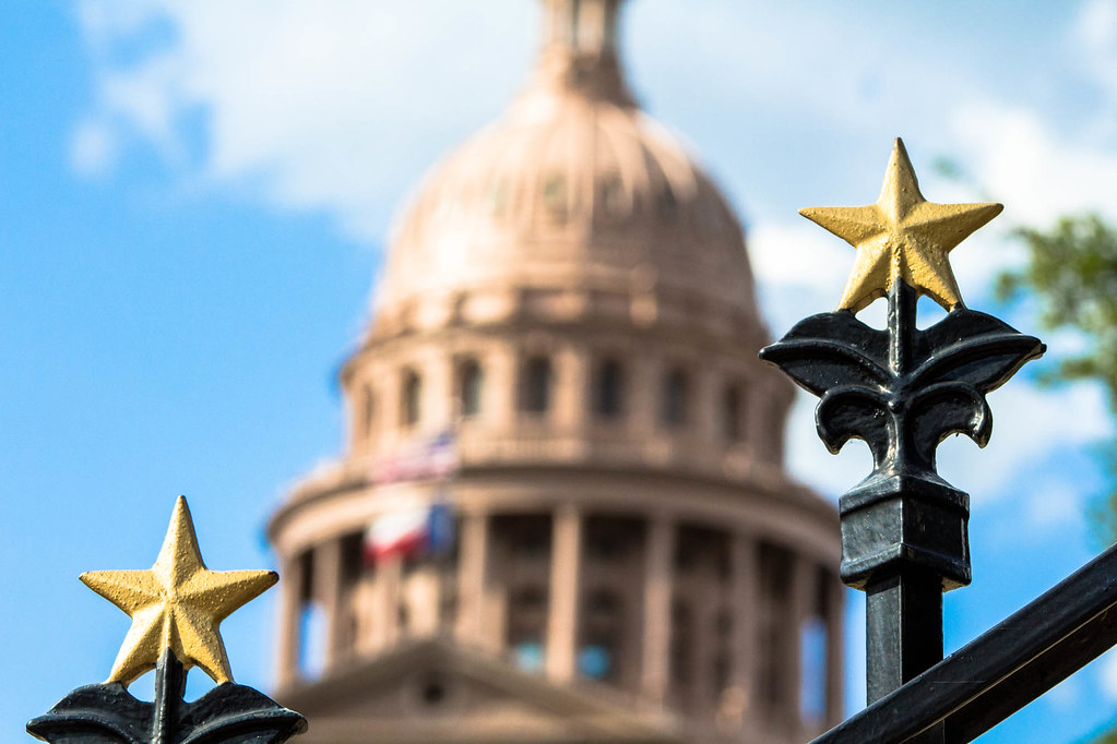 Ornamental stars top a fence in the foreground with the Texas State Capitol dome unfocused in the distant background